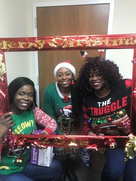 Beaufort staff memebers posing in their Christmas sweaters holding a red frame.