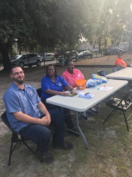 Beaufort Staff members participating in national night out with local law enforcement sitting at a table.